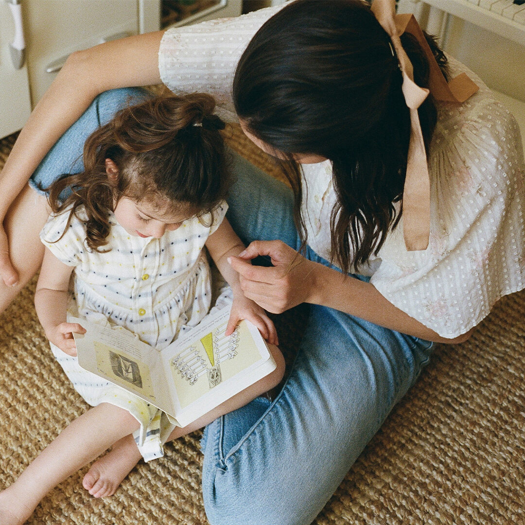 A mother and her daughter sitting and reading a book