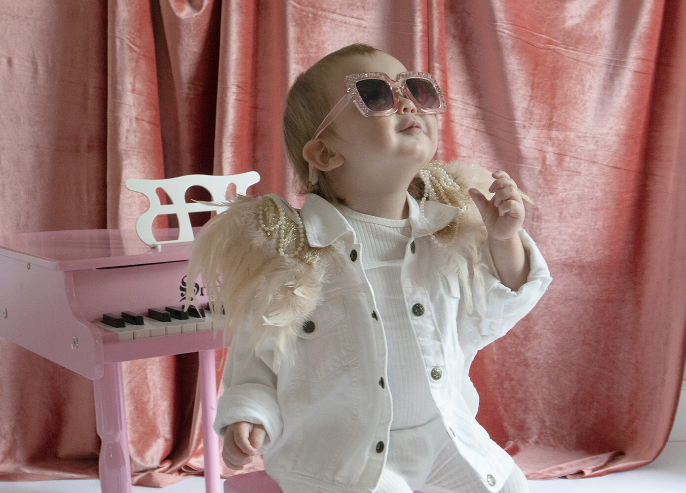 baby in glam sunglasses dressed as Elton John at a piano