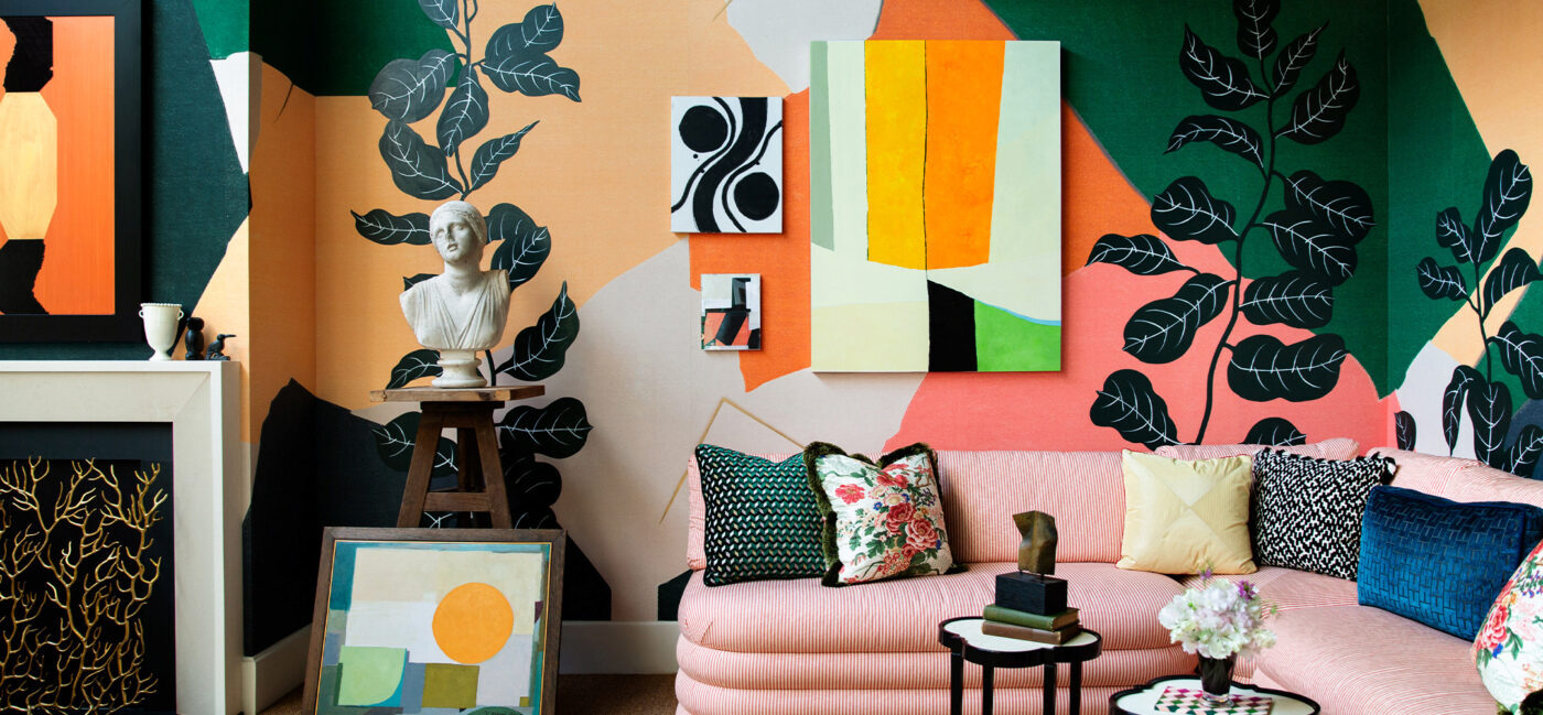 A beautifully decorated room with pink, yellow, and orange wallpaper, a bust on a stool, and a pink couch