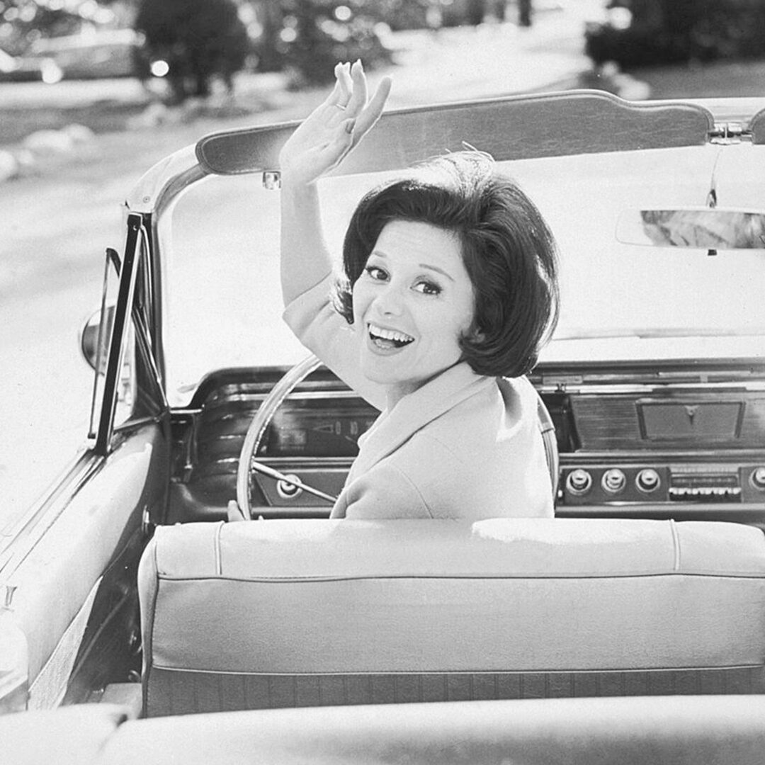 black and white image of a woman in a convertible turning around and waving
