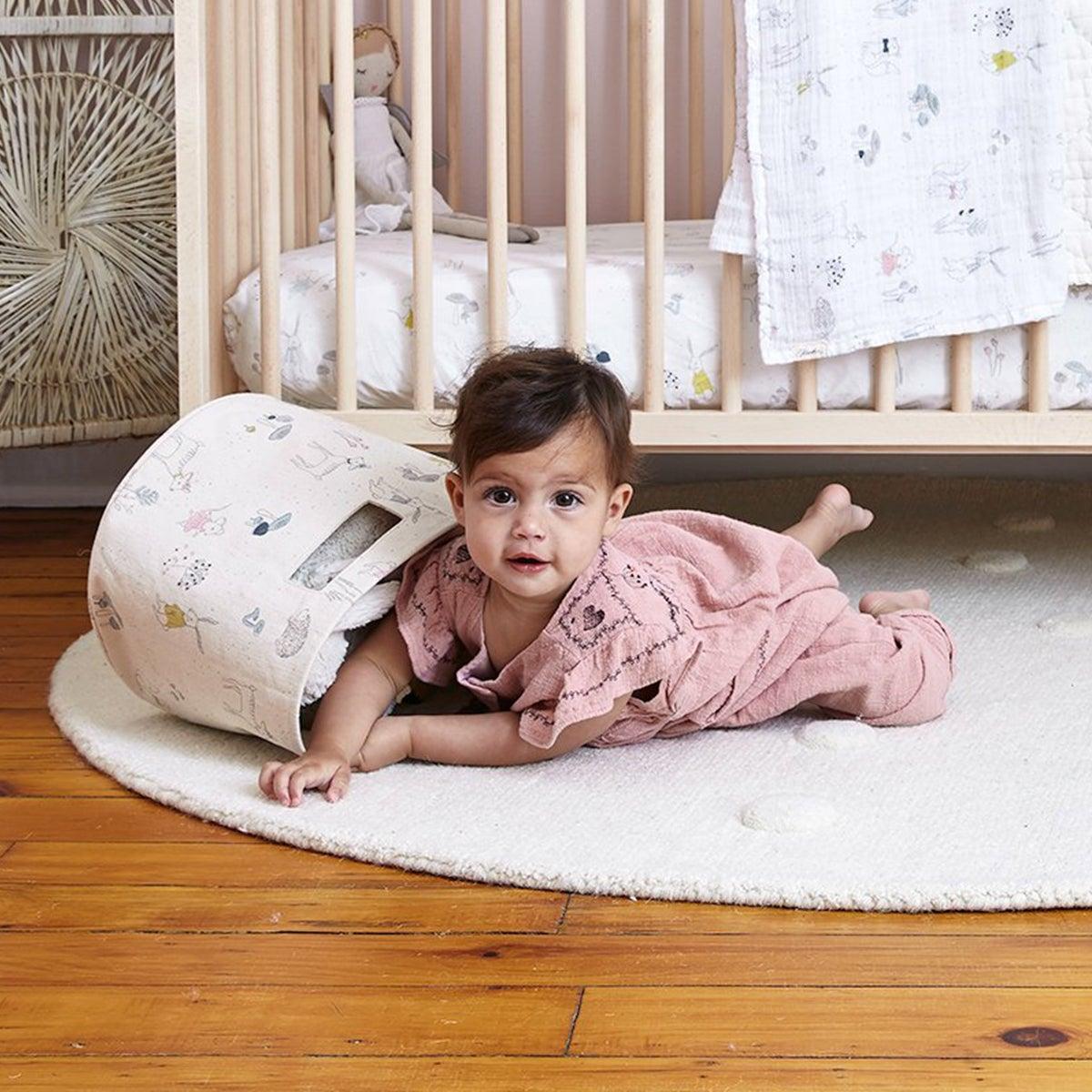 A baby crawling next to a crib
