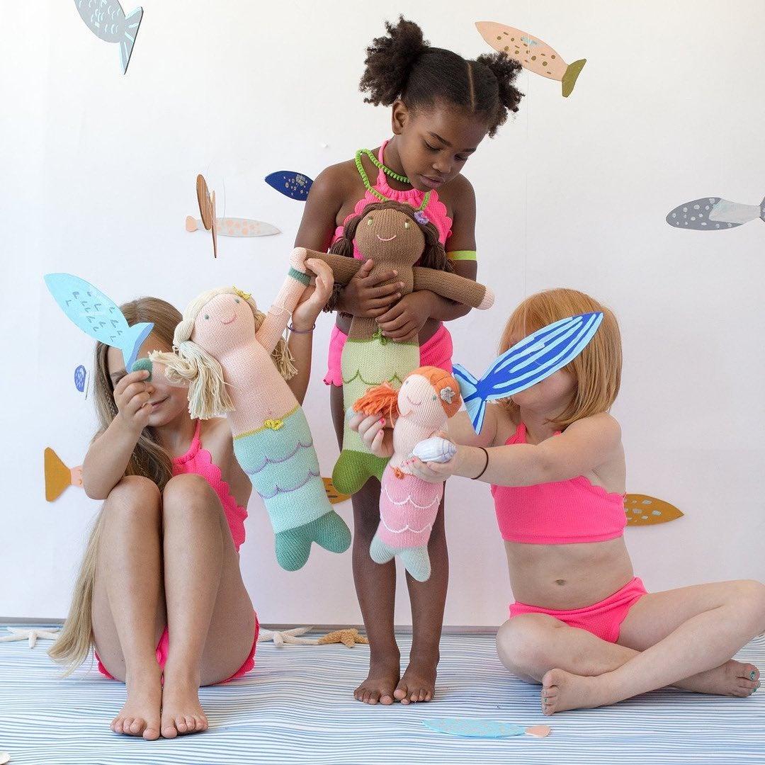 three girls with mermaid dolls in similar skin tones