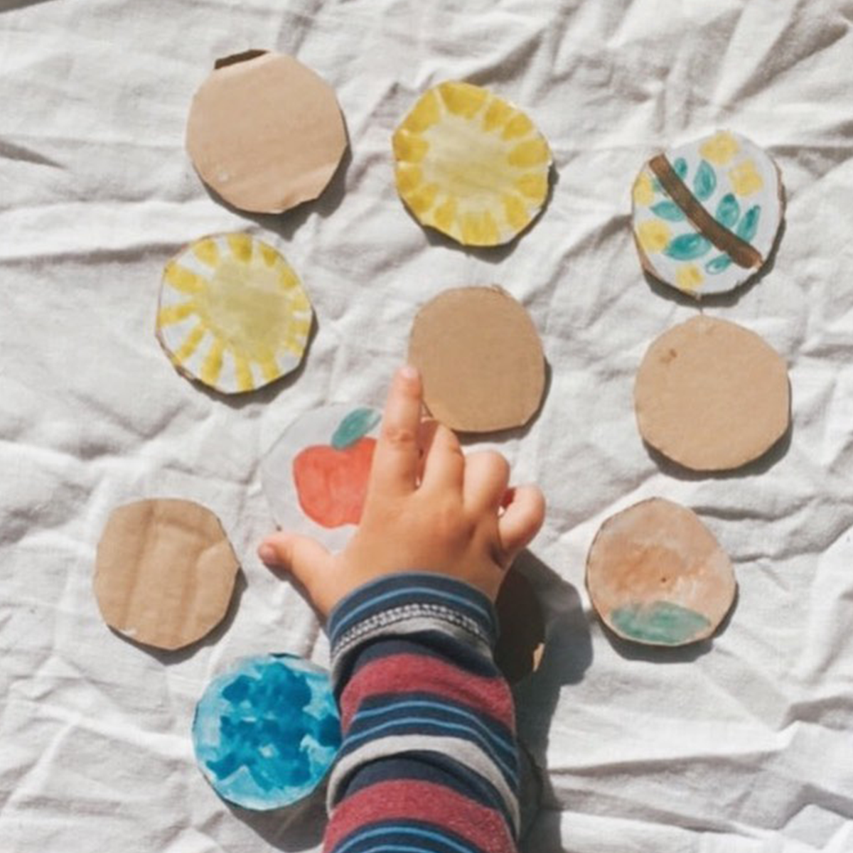 child reaching for a painted memory game created with cardboard and paint