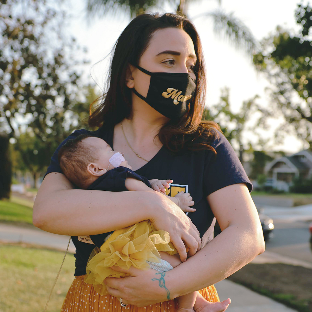 Britni Soto holding her baby Gracie while wearing a mask